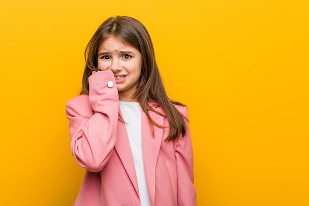 Niña linda caucásica morderse las uñas, nervioso y muy ansioso.
