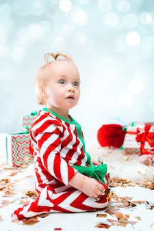 Niña linda cerca de sombrero de santa posando sobre fondo de navidad con decoración. sentado en el suelo con bola de navidad.