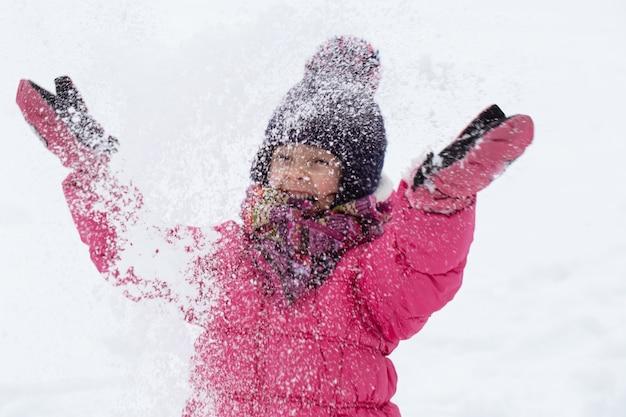 Una niña linda con una chaqueta rosa y un sombrero está jugando en la nieve. concepto de entretenimiento infantil de invierno.