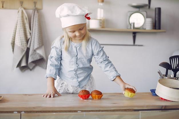 Niña linda en una cocina con cupcake