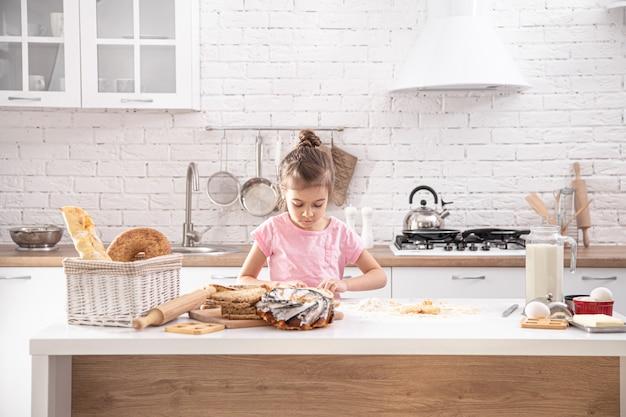 Niña linda está cocinando pasteles caseros en la cocina.