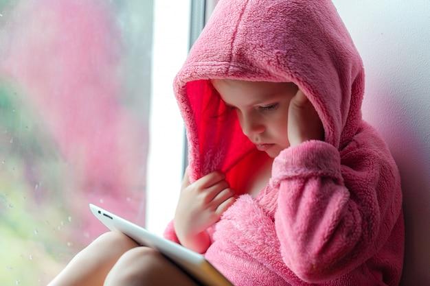 Niña linda con cola de caballo en bata de baño rosa viendo los medios en una tableta