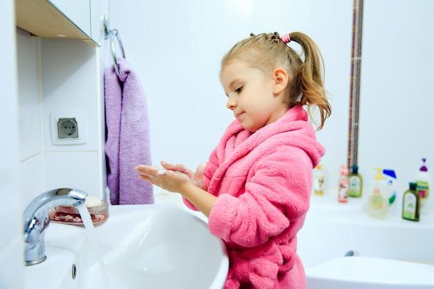 Niña linda con cola de caballo en bata de baño rosa