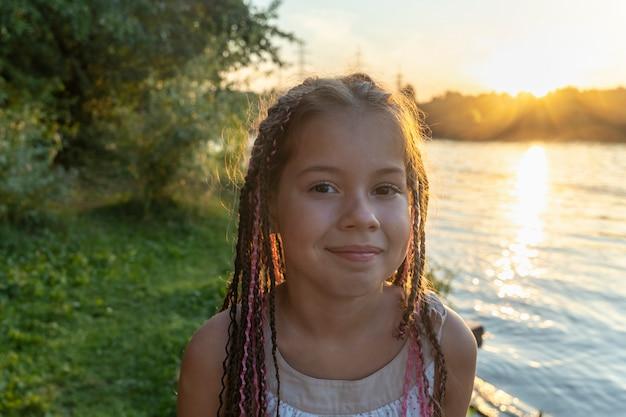 Niña linda con coletas africanas en el fondo del lago y la playa en primer plano mira misteriosamente a la cámara. hermosa puesta de sol en el parque junto al río. infancia feliz. vacaciones escolares.