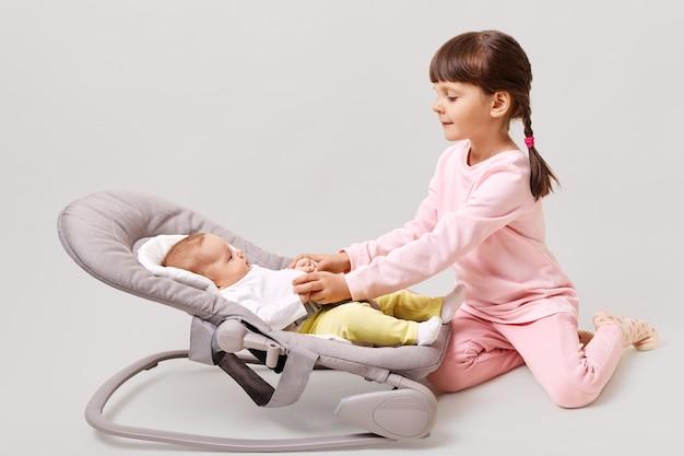 Niña linda con coletas jugando con su hermana recién nacida mientras está sentada en el piso aislado sobre la superficie blanca