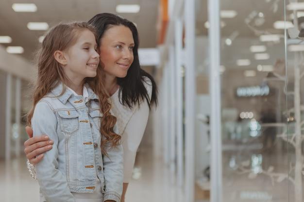 Niña linda de compras en el centro comercial con su madre