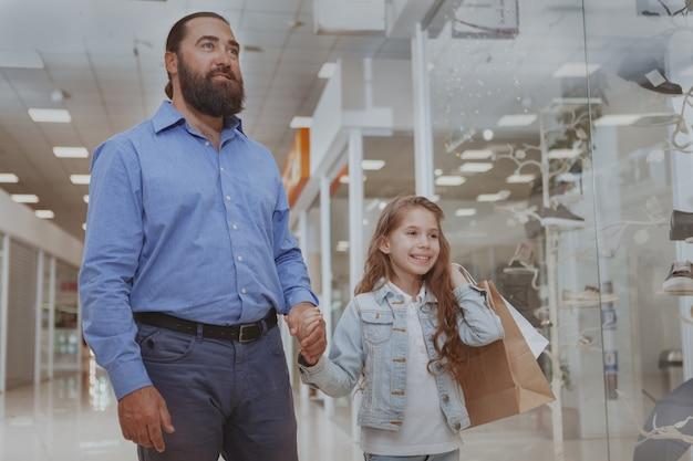 Niña linda de compras en el centro comercial con su padre