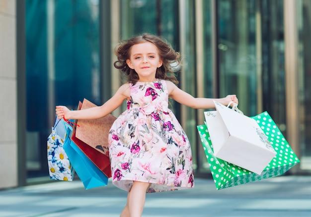 Niña linda en compras. retrato de un niño con bolsas de compras. compras. niña.