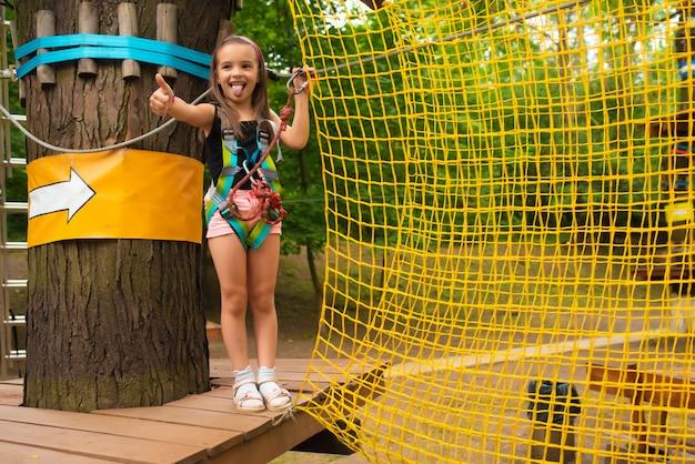 Niña linda corre una carrera de obstáculos en un parque de cuerdas