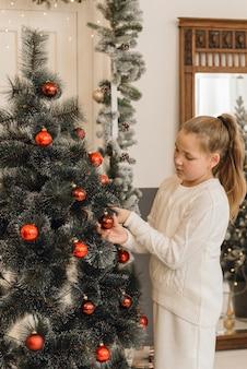 Niña linda decora el árbol de navidad con juguetes de año nuevo y bolas rojas. una niña con un suéter de punto blanco y un vestido está colgando bolas colgando de un abeto artificial