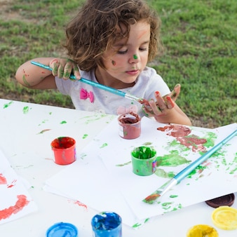 Niña linda dibujo pintura sobre lienzo en el parque
