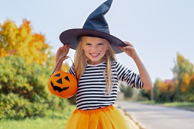 Niña linda en un disfraz de bruja de halloween