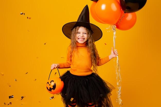 Niña linda en un disfraz de bruja para halloween