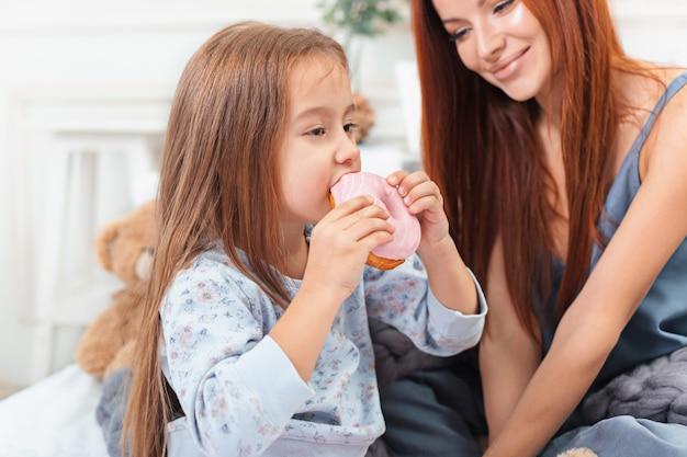 Una niña linda disfrutando, jugando y creando con pastel con madre