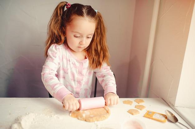 La niña linda se divierte en una cocina