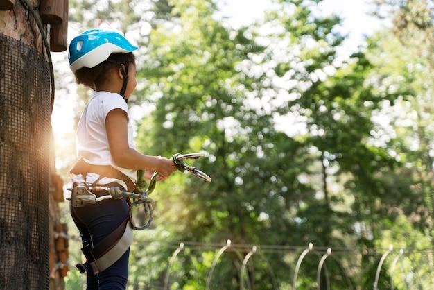 Niña linda divirtiéndose en un parque de aventuras