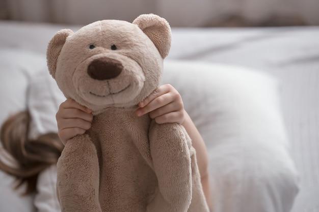 Niña linda duerme dulcemente en una acogedora cama blanca con un osito de peluche, el concepto de descanso y sueño de los niños
