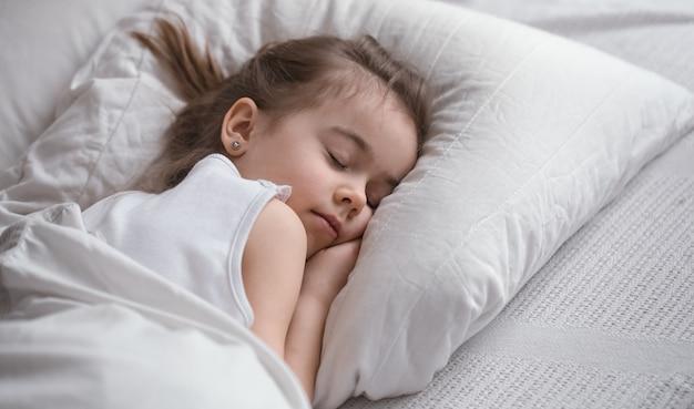 Niña linda duerme dulcemente en la cama