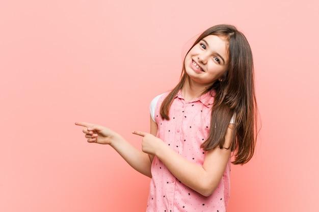 Niña linda emocionada señalando con los dedos lejos.