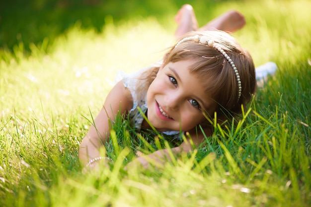 Niña linda se encuentra en el césped en el parque de verano