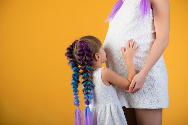 La niña linda entrecerró los ojos con astucia y escucha el vientre embarazado de la madre sobre un fondo amarillo