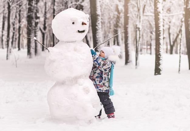 Niña linda esculpe un gran muñeco de nieve en invierno en el parque