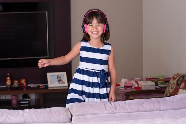 Niña linda feliz escuchando música en el sofá en casa.
