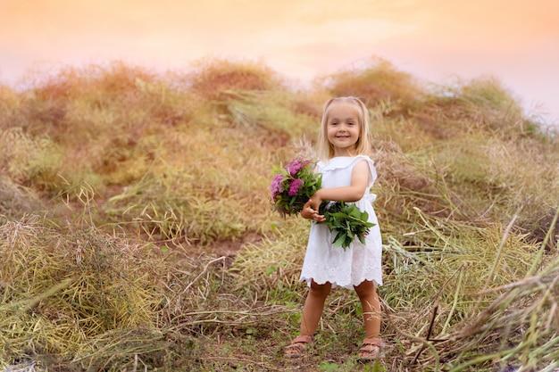 La niña linda feliz está llevando el vestido blanco que se coloca en el campo y que sostiene el ramo de flores rosadas
