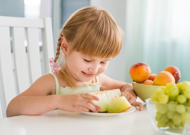 Niña linda con frutas en la mesa
