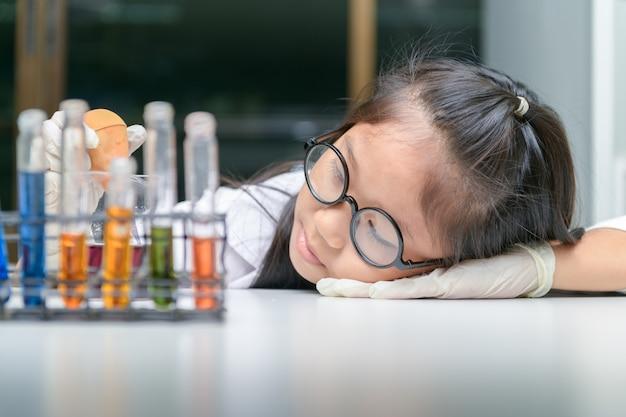 Niña linda con gafas y bata de laboratorio haciendo experimento