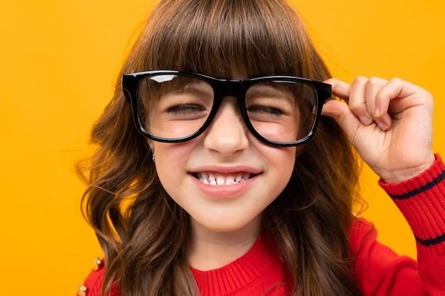 Niña linda en gafas entrecerrar los ojos de cerca en naranja