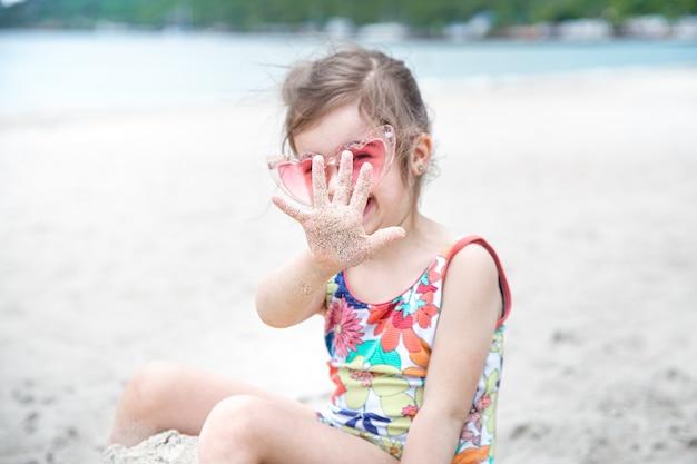 Una niña linda con gafas está jugando en la arena de la playa junto al mar.
