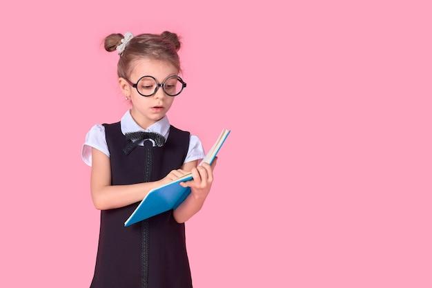 Niña linda con gafas y libros sobre espacio rosa, espacio para texto. concepto de lectura