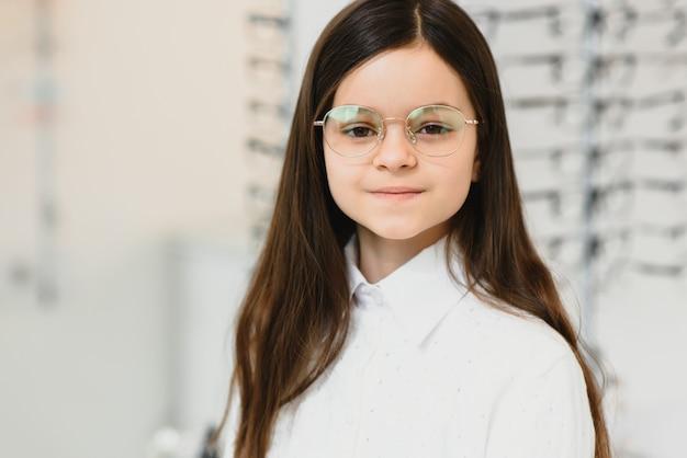 Niña linda con gafas nuevas en la tienda