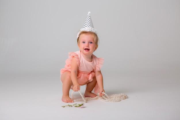 Niña linda en gorro de cumpleaños en luz