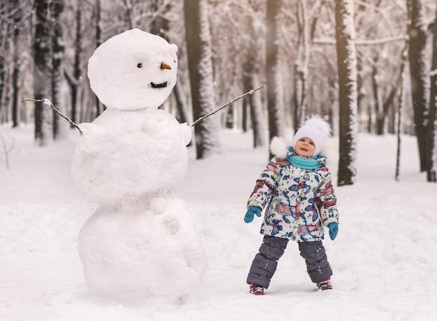 Niña linda y un gran muñeco de nieve de invierno en el parque