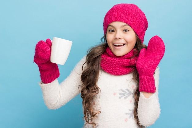 Niña linda con guantes y sombrero sosteniendo una taza