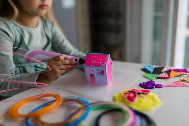 La niña linda hace una casa de plástico, dibuja piezas con un bolígrafo 3d. desarrollo, modelado, educación, diseño con plástico caliente. tecnologías modernas bricolaje.