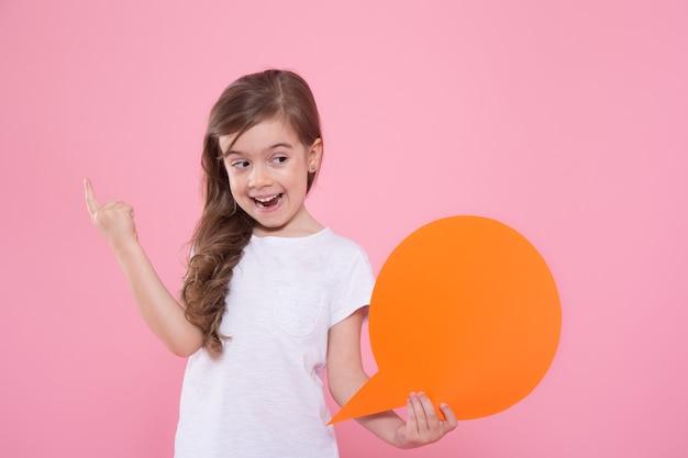 Niña linda con un icono de un discurso en una pared rosa