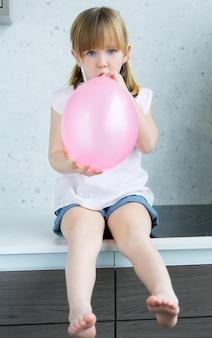 Niña linda inflar un globo de color rosa en la cocina