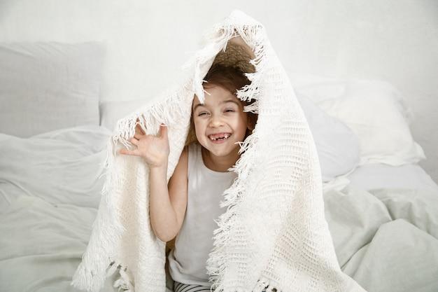 Niña linda jugando en la cama con una manta después de dormir