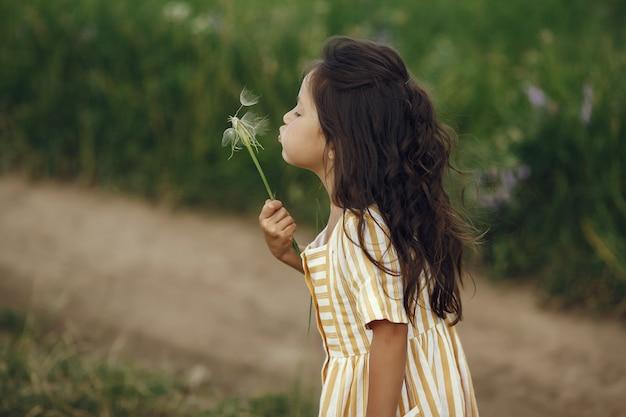 Niña linda jugando en un campo de verano