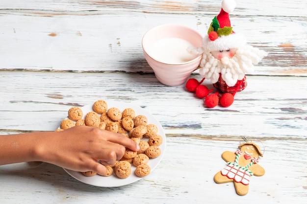 Niña linda está jugando con las galletas y la leche de santa claus en navidad
