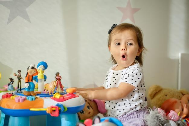 Niña linda jugando con muchos juguetes que se encuentran en una sala de juegos.