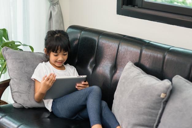 Niña linda jugando en una tableta y viendo dibujos animados