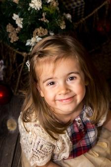 Niña linda con un juguete santa en manos se sienta en un piso de madera con decoración navideña