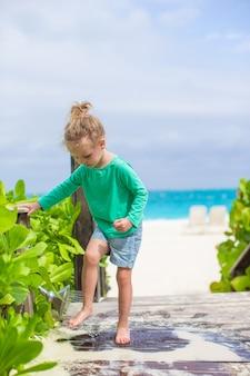 Niña linda lava la arena de sus pies en la playa tropical