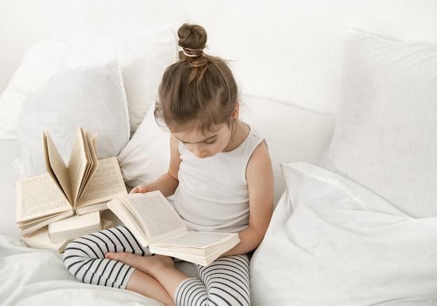 Niña linda leyendo un libro en la cama en el dormitorio.