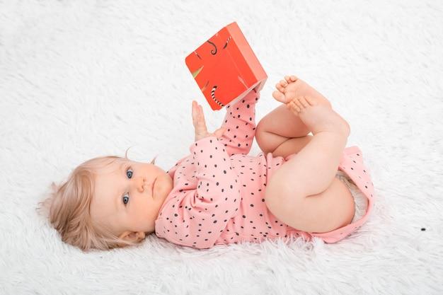 Niña linda con el libro en la habitación de los padres.
