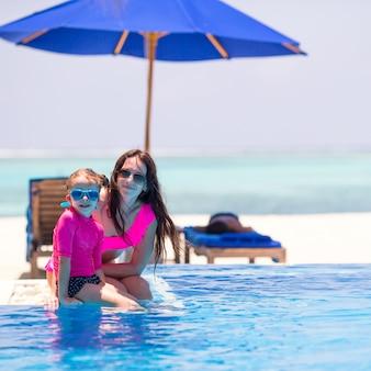 Niña linda y madre feliz disfrutando de vacaciones en la piscina al aire libre